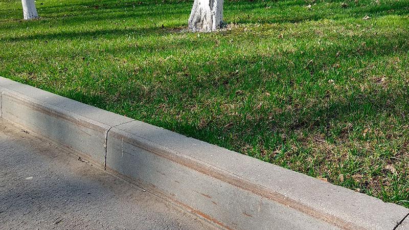 На бордюрном камне видны ржавые следы механического воздействия - уборка в парке производится спецтехникой